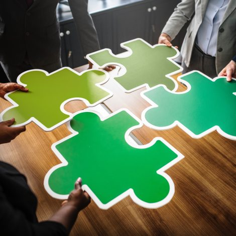 people fitting together large colored puzzle pieces